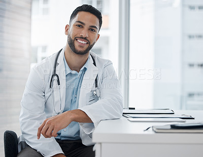 Buy stock photo Shot of a young doctor sitting at a desk in an office