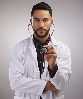 Buy stock photo Shot of a handsome young doctor standing alone in the studio and holding a stethoscope