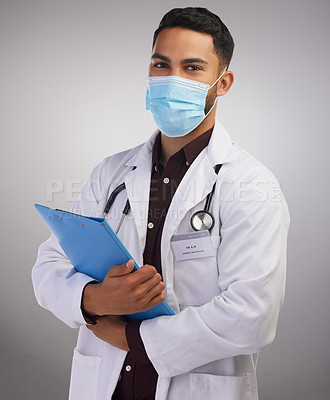 Buy stock photo Shot of a handsome young doctor standing alone in the studio and wearing a face mask while holding a clipboard