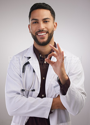 Buy stock photo Shot of a handsome young doctor standing alone in the studio and making an okay hand gesture