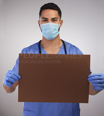 Buy stock photo Shot of a handsome young nurse standing in the studio and holding up a poster while wearing a face mask