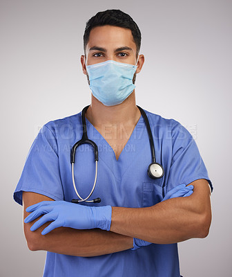 Buy stock photo Shot of a handsome young nurse standing alone in the studio with his arms folded and wearing a face mask