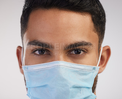 Buy stock photo Shot of a handsome young nurse standing alone in the studio and wearing a face mask