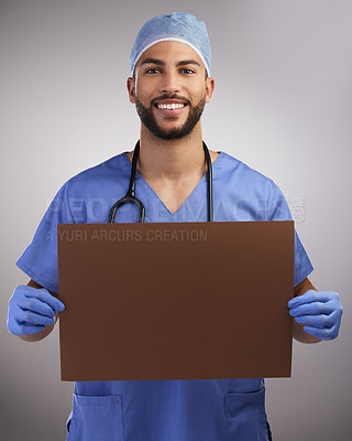 Buy stock photo Shot of a handsome young nurse standing alone in the studio and holding up a poster