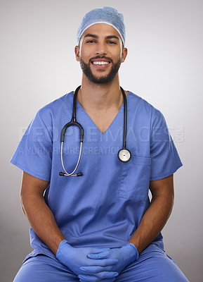 Buy stock photo Shot of a handsome young nurse sitting alone in the studio