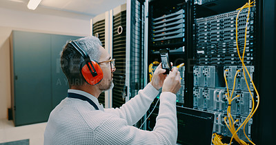 Buy stock photo Shot of a male technician using his smartphone to take a photo in a server room