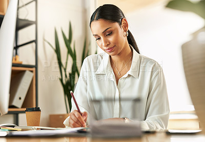 Buy stock photo Shot of a young businesswoman compiling notes at work