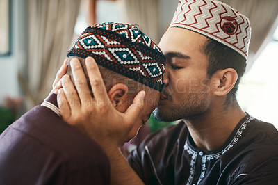 Buy stock photo Shot of a young muslim father affectionately giving his son a forehead kiss