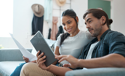 Buy stock photo Shot of a young couple doing paperwork while using a digital tablet at home