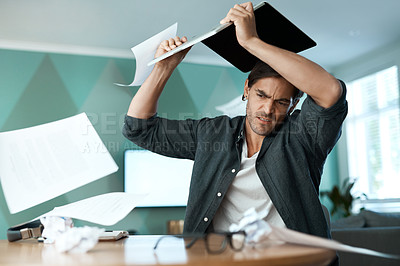 Buy stock photo Shot of a young man smashing a laptop on a table at home