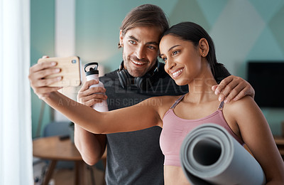 Buy stock photo Cropped shot of an athletic young couple taking selfies before starting their workout at home
