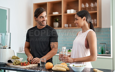 Buy stock photo Cropped shot of an affectionate young couple making smoothies in their kitchen at home