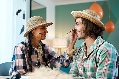 Buy stock photo Shot of a young woman applying makeup to a young man at home