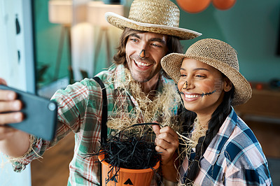 Buy stock photo Shot of a young couple taking selfies while holding buckets at home