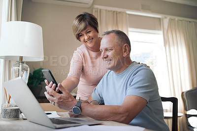 Buy stock photo Shot of a mature husband and wife together using a smartphone