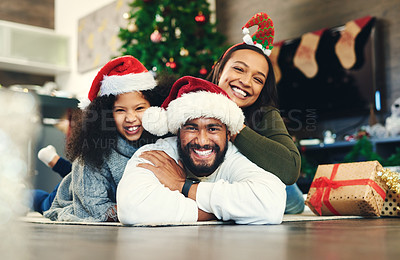 Buy stock photo Portrait of a happy young family celebrating Christmas at home