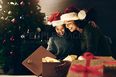 Buy stock photo Shot of a cute little girl opening presents with her mother during Christmas at home
