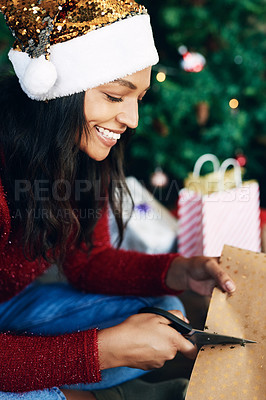 Buy stock photo Shot of a young woman wrapping Christmas gifts at home