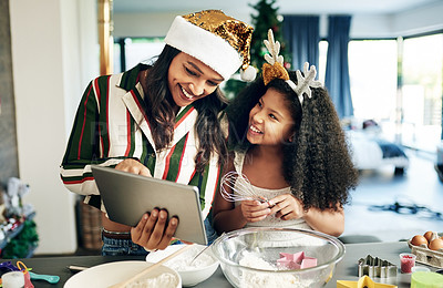Buy stock photo Shot of a happy young mother and daughter using a digital tablet while preparing a meal during Christmas at home