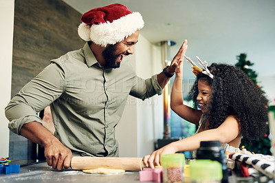 Buy stock photo Shot of a happy young father and daughter baking during Christmas at home