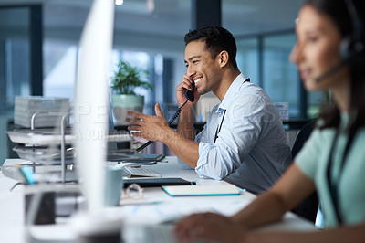 Buy stock photo Shot of a young man answering the phone while working in a modern call centre
