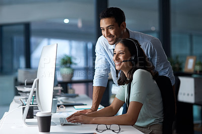 Buy stock photo Shot of a young man and woman using a computer while working in a call centre