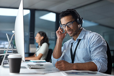 Buy stock photo Shot of a young man using a headset and computer in a modern office