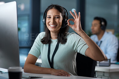 Buy stock photo Portrait of a young woman using a headset and showing an okay gesture in a modern office