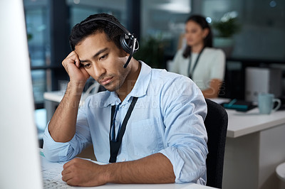 Buy stock photo Shot of a young man using a headset and looking depressed in a modern office