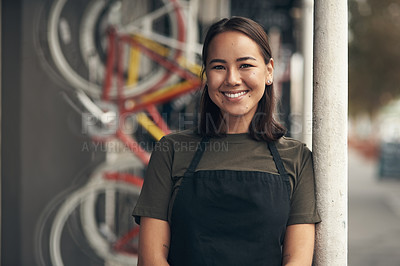 Buy stock photo Shot of an attractive young woman standing outside her bicycle shop during the day