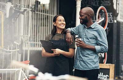 Buy stock photo Shot of two young business owners standing outside their bicycle shop during the day