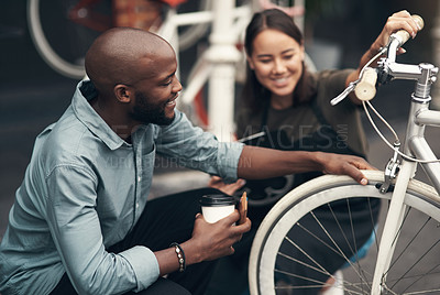 Buy stock photo Shot of an attractive young woman crouching outside her bicycle shop and assisting a customer