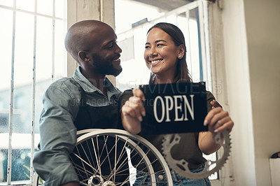 Buy stock photo Shot of two young business owners standing together in their bicycle shop and holding an open sign