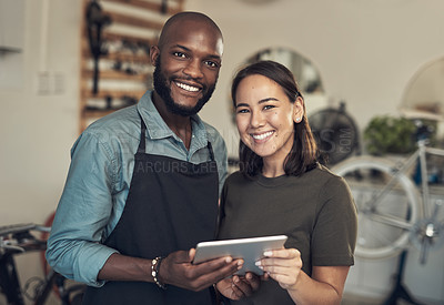 Buy stock photo Shot of two young business owners standing together in their bicycle shop and using a digital tablet