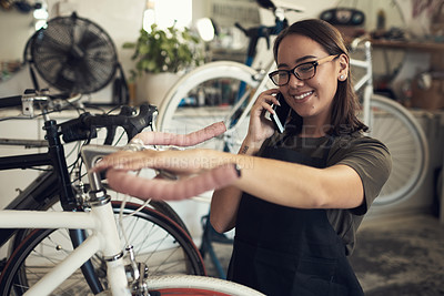 Buy stock photo Shot of an attractive young woman standing alone in her shop and repairing a bicycle wheel while using her cellphone