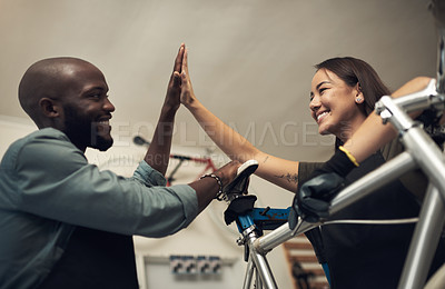 Buy stock photo Shot of two young business owners standing together in their bicycle shop and giving each other a high five