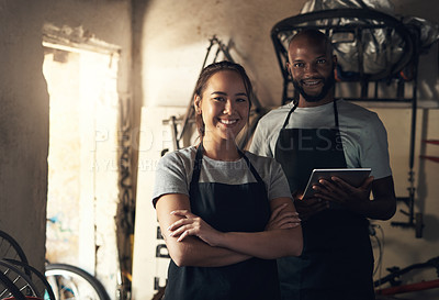 Buy stock photo Portrait of two young people working at a bicycle repair shop