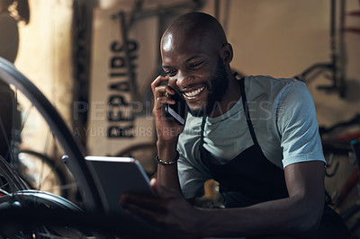 Buy stock photo Shot of a young man talking on a cellphone and holding a digital tablet while working at a bicycle repair shop