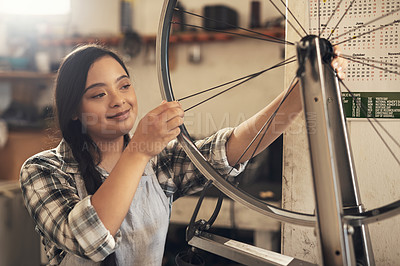Buy stock photo Shot of a young woman working on a bike at a bicycle repair shop