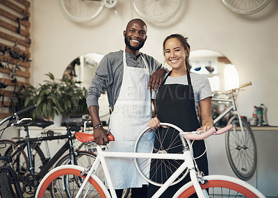 Buy stock photo Portrait of two young workers holding a bike at a bicycle repair shop