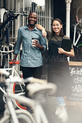 Buy stock photo Full length shot of two young business owners standing outside their bicycle shop during the day