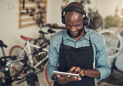 Buy stock photo Shot of a handsome young man standing alone in his bicycle shop and using a digital tablet while wearing headphones