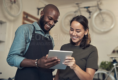 Buy stock photo Shot of two young colleagues standing together in their bicycle shop and using a digital tablet