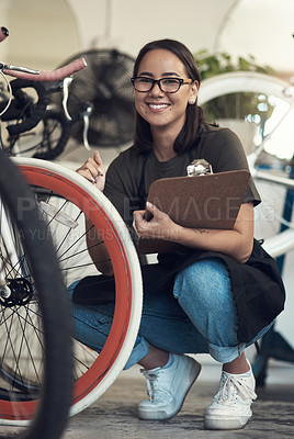 Buy stock photo Full length shot of an attractive young woman crouching in her bicycle shop and holding a clipboard