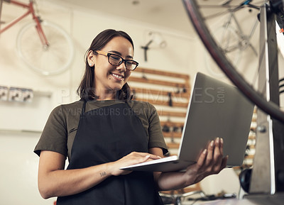 Buy stock photo Shot of an attractive young woman standing alone in her bicycle shop and using her laptop