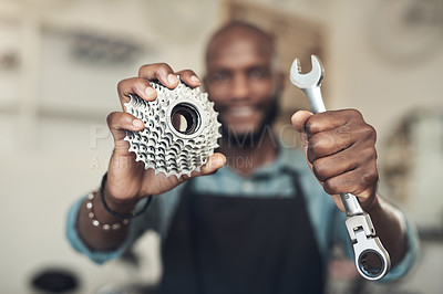 Buy stock photo Shot of an unrecognizable man standing alone in his bicycle shop while holding a spanner and bicycle cassette
