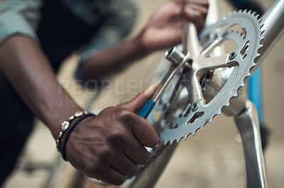Buy stock photo Shot of an unrecognizable man standing alone in his shop and repairing a bicycle wheel