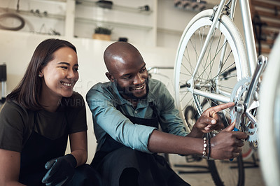 Buy stock photo Shot of two young business owners crouching in their shop and fixing a bicycle wheel