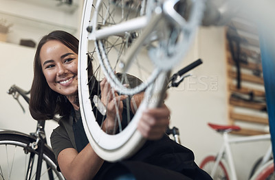 Buy stock photo Shot of an attractive young woman crouching alone in her shop and repairing a bicycle wheel