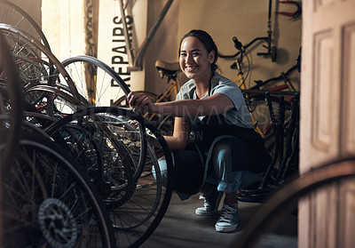 Buy stock photo Portrait of a young happy young woman fixing a bike at a bicycle repair shop